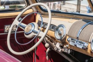 Classic car interior with white and silver metal steering wheel and dashboard with gauges and radio, woodtone door