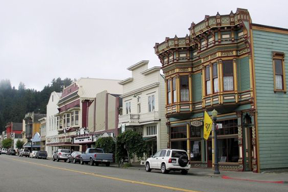 Row of two-story Victorian buildings - green with bay windows and gold trim, gray with balconies, burgundy, etc.- Ferndale, CA.