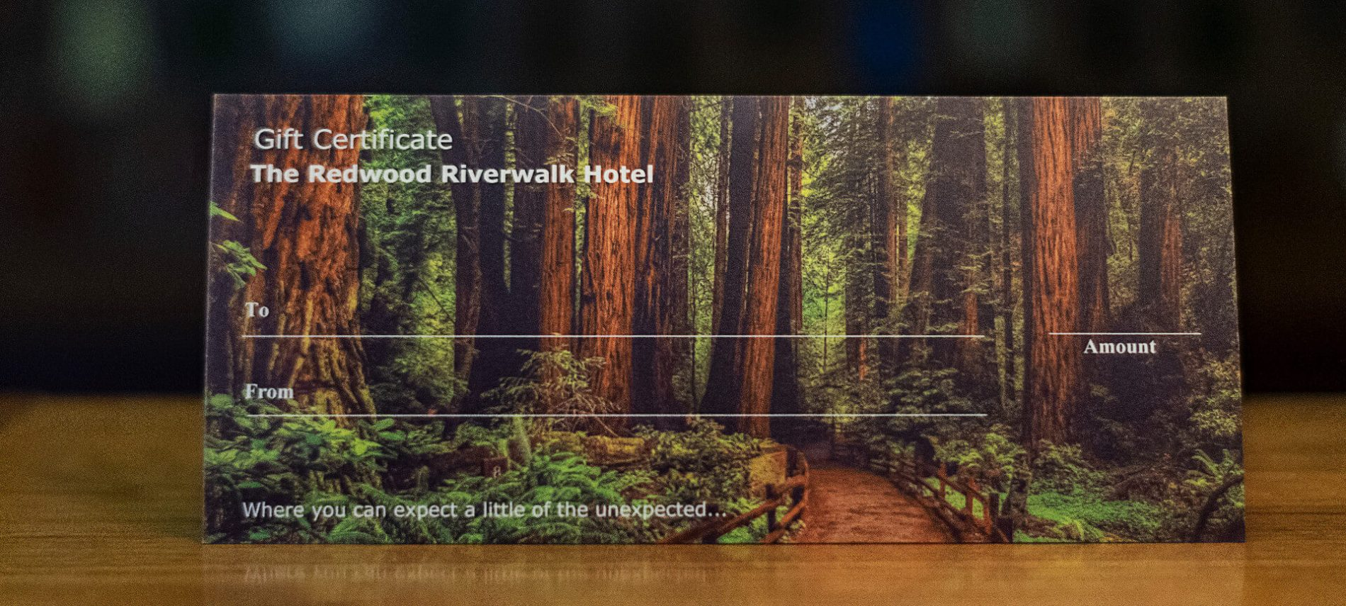 Paper Gift Certificate on redwood tree paper sitting on wooden desk with black background