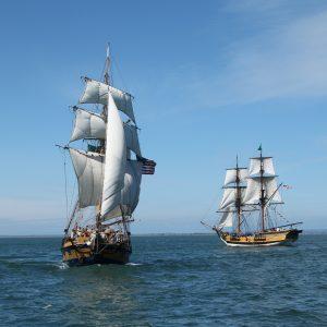 Gray's Harbor Historical Seaport's Topsail Ketch Hawaiian Chieftain & Brig Lady Washington, under sail on blue ocean, cloudless sky