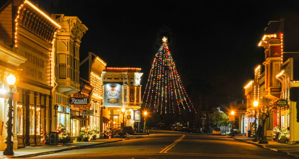 Ferndale Victorian buildings outlined in white lights at night, vertical multicolored lights on tallest Christmas Tree at end of street