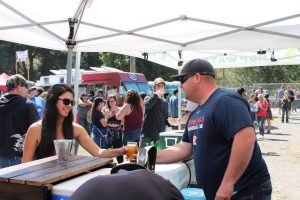 woman with dark hair wearing sunglasses handing glass of beer to man in ballcap under white tent, crowd behind them