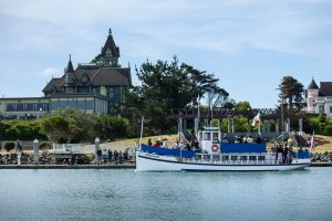 Madaket blue & white ferry boat sailing in bay with people watching from quay and Victorian mansion & green trees behind