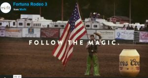 Follow the Magic: Fortuna Rodeo: Cowboy standing in rodeo ring beside big yellow Coors can, holding American flag and waving hat, billboard wall, white trailers behind