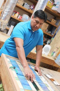 man in blue polo laying out blue rectangular stained glass pattern on wood table with storage shelves and table behind
