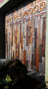"""The Redwood Riverwalk Hotel"" - 8' tall sign made of 100+ different length vertical boards of recycled red, brown, grey redwood"