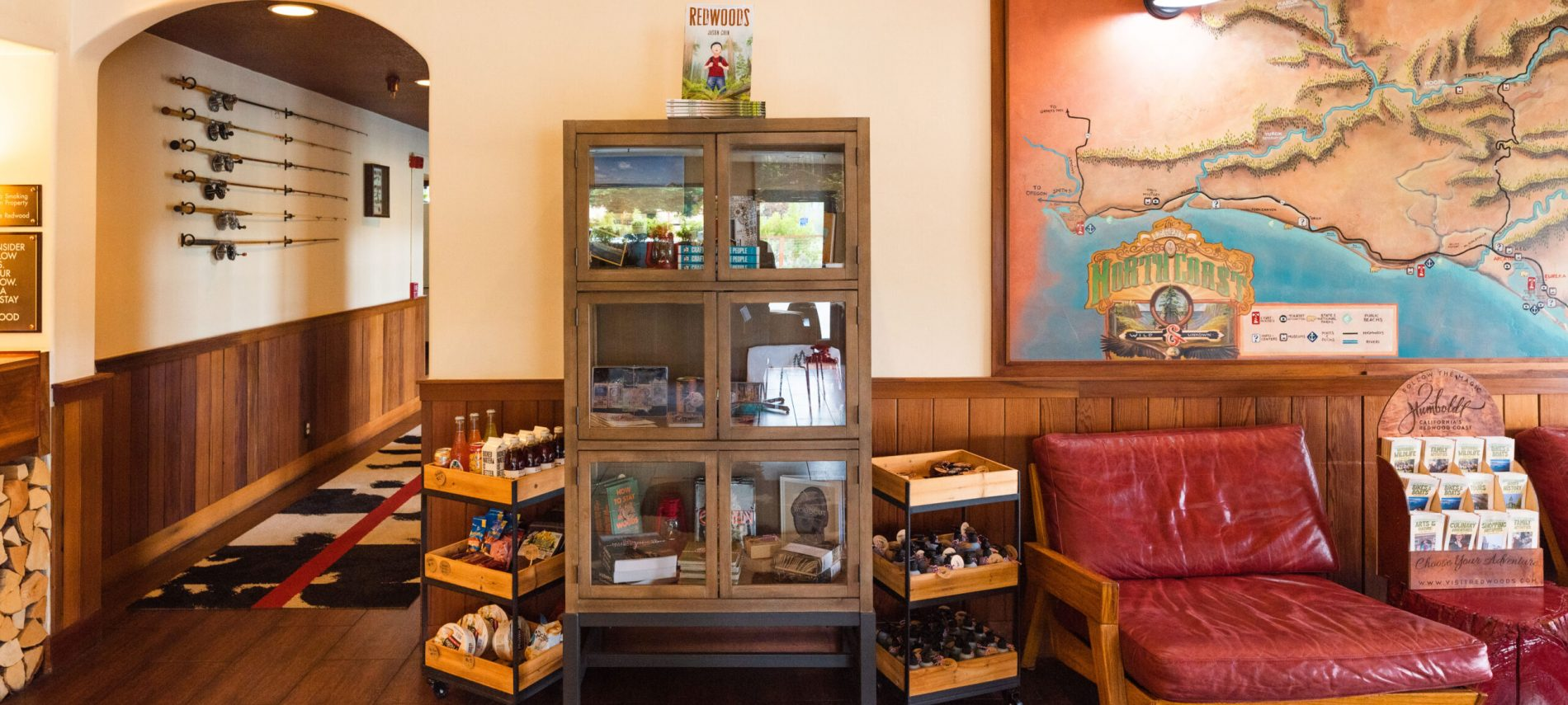 TR Mercantile lobby with tall wood cabinet map on wall behind chair with red cusions