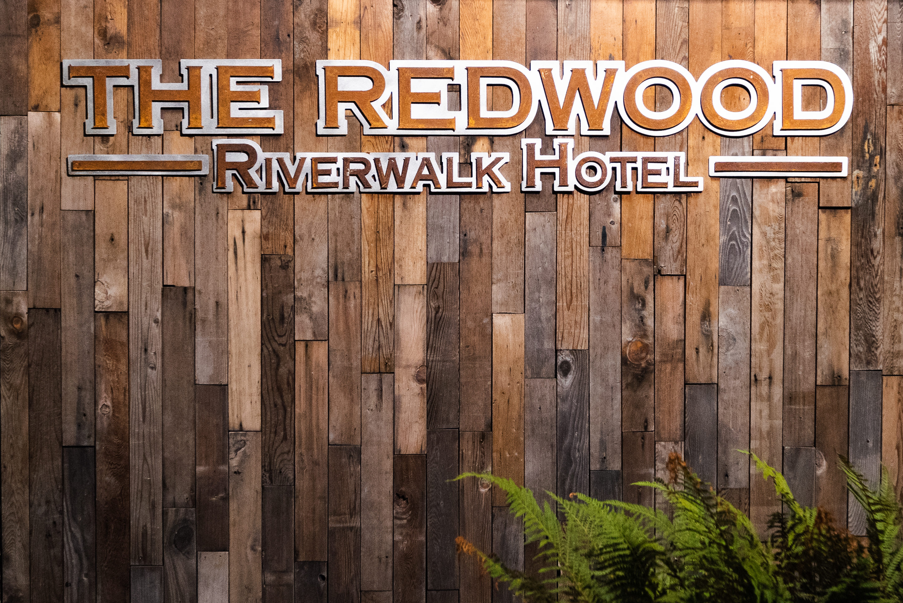 vertical pieces of varied redwood making sign text:: The Redwood Riverwalk Hotel