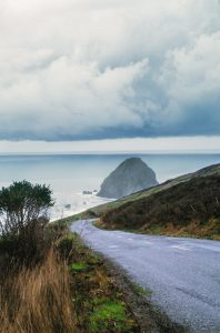 Gray road bordered by grasses and shrubs curving down and around bend toward Pacific, triangular rock offshore under cloudy sky