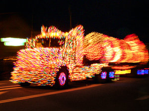 Flatbed truck covered with multicolored Christmas lights on cab and cargo, lighted purple / blue wheels - Lighted Truck Parade - by Todoroff