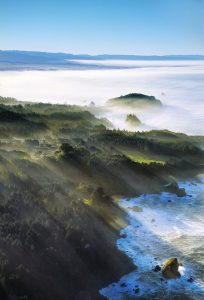 aerial of Trinidad Head sunrise with white waves below and sun rays streaking through low clouds