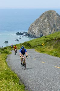 three bicycle riders ride up steep hill on trail bordered by grasses, blue Pacific and large gray rock behind