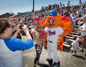 Woman holding young boy having picture with Humboldt Crabs mascot wearing orange & red crab costume Fans in stands behind