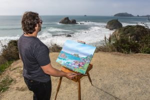 man in gray t-shirt and jeans standing on beach looking over crashing waves, rock formations to paint seascape on easel