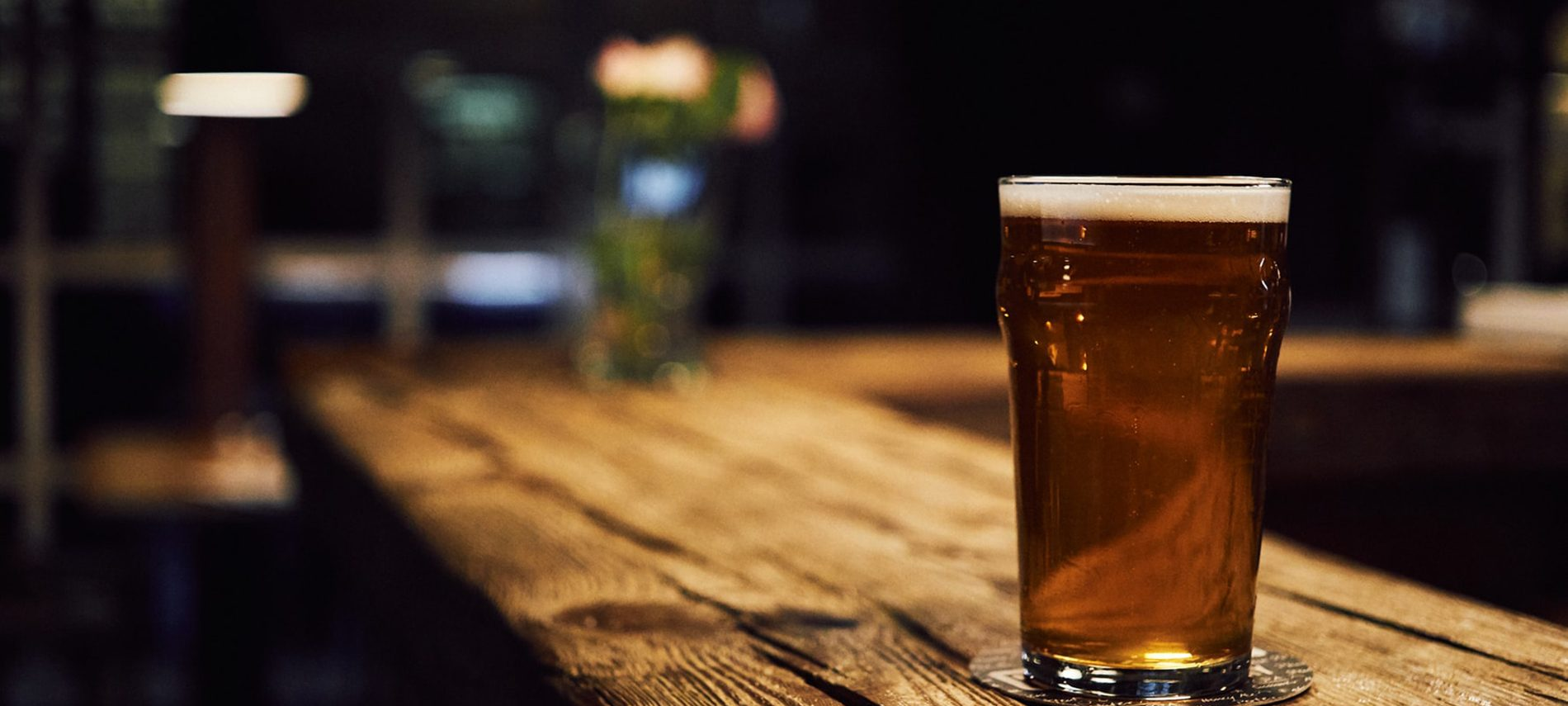 glass of golden beer with white head on long wooden bar