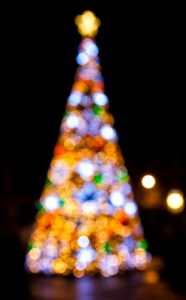 Blurred night exposure of multicolored lighted Christmas tree with gold star on top