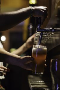 hands holding beer glass while filling from beer tap