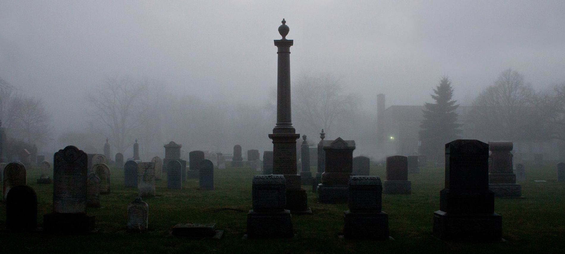 cemetery with many gravestones and a tall monument in dark foggy mist light in distant building