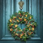 Holiday wreath with red and yellow fruit decorations hanging on blue-green paneled door