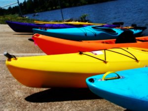 four kayaks - blue yellow orange blue on beach with water in background