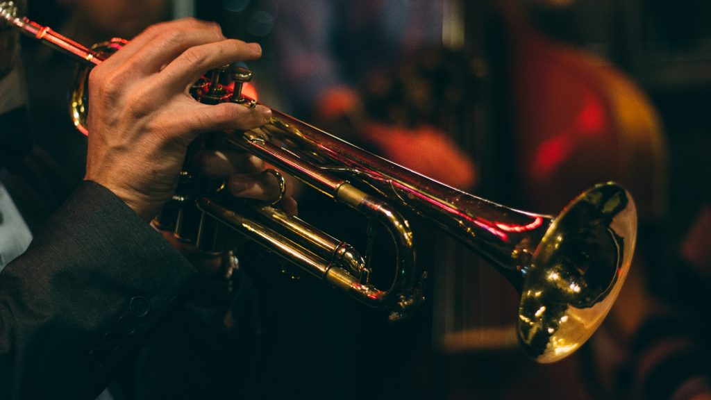 closeup of man's right hand fingers playing brass trumpet at night with red light behind