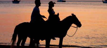 Silhouette of a couple on horseback on the beach against a sunset backdrop