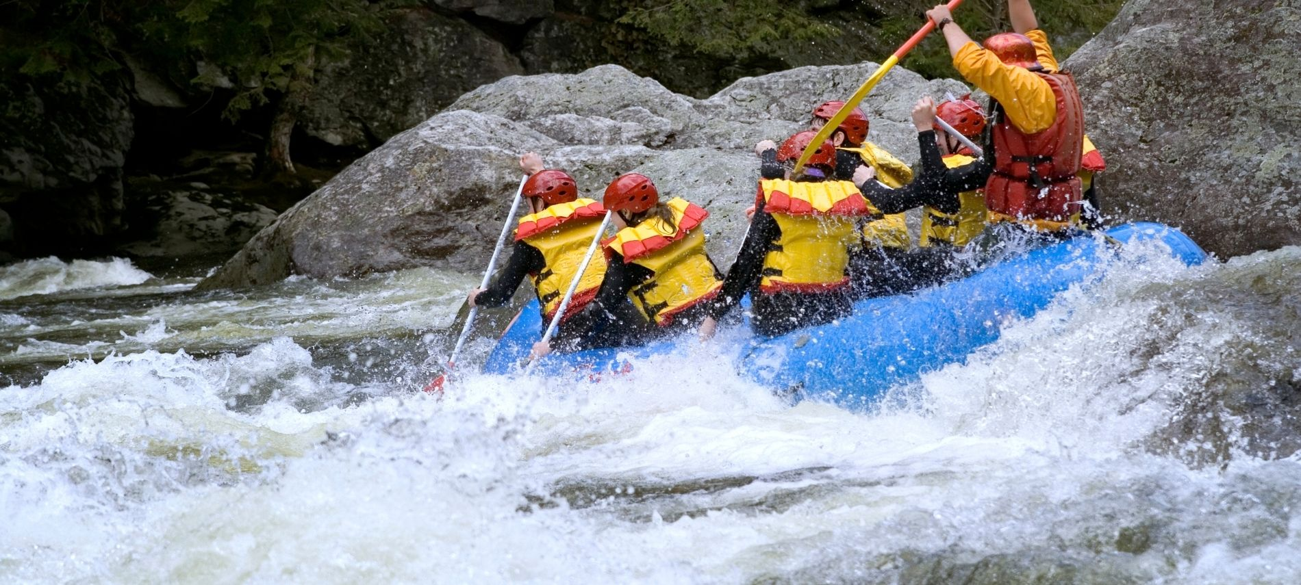 Group of people white water river rafting