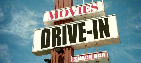 Large outdoor sign that says Movies, Drive-In, Snack Bar