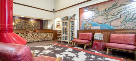 Beautiful Lobby with area rug, large wall map, upholstered chairs, and stone desk and counter