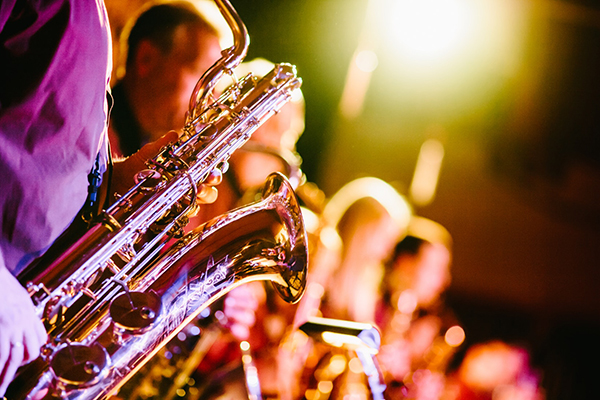Closeup of person in pink shirt playing brass saxophone in bright stage lights with other musicians out of focus in background