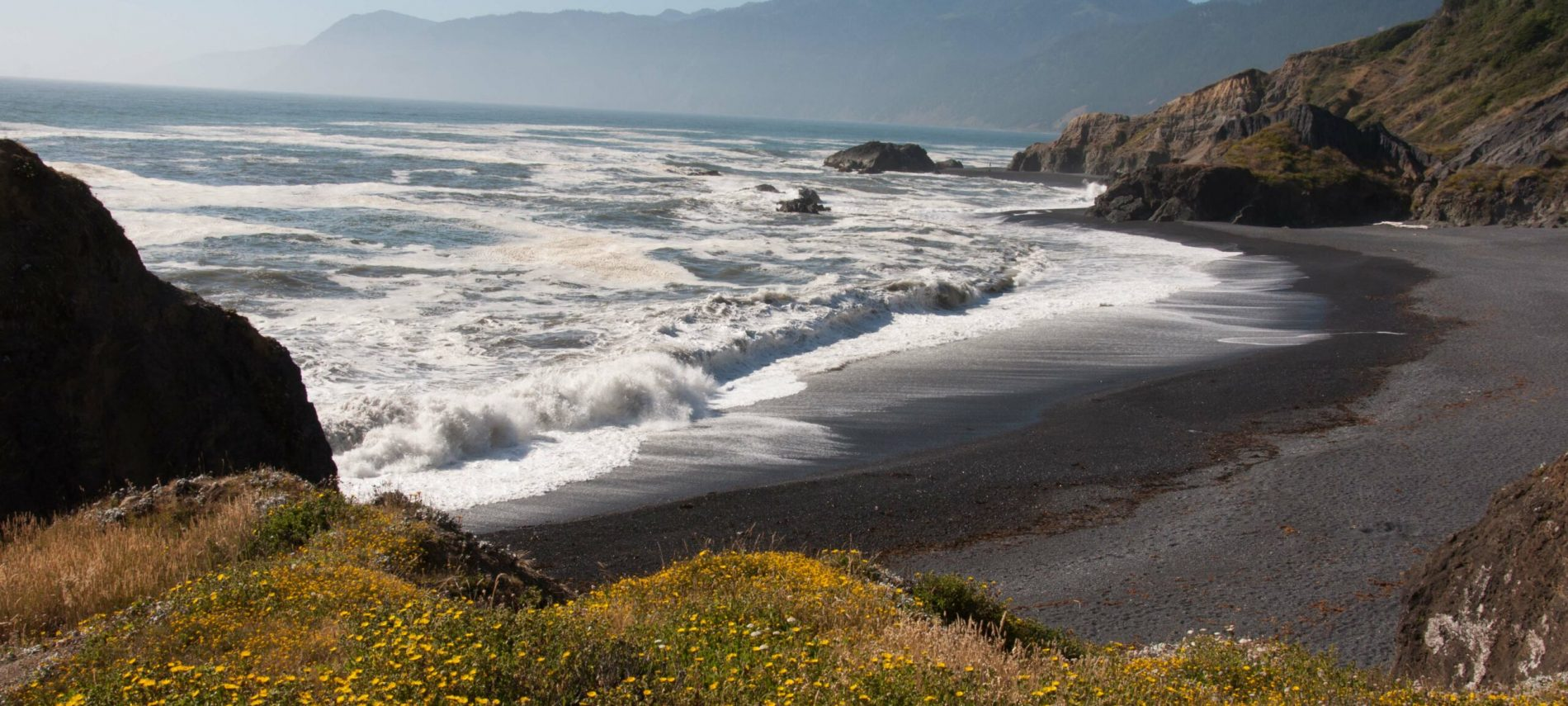 view from hill of black sands beach with surf crashing and silhouette of mountains in background