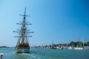 tall ship sailing on blue humboldt bay with boats anchored on shoreline