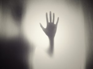 shadowy ghostly gray hand held up with fingers spread surrounded by pale fog