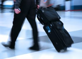 A man with suitcase depicting movement through an airport or public space.