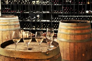 5 glasses of white wine on wine barrel top with barrels on either side and racks of wine bottles behind