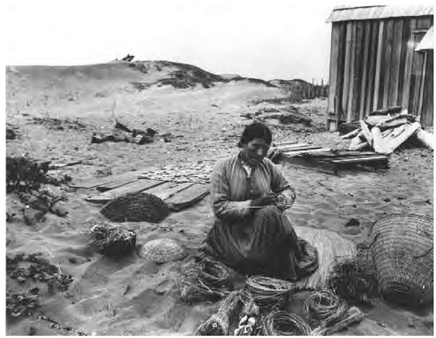 Black and white photograph of Wiyot woman making baskets outside